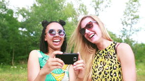 Two young women having a great time taking selfies. Close up of two beautiful young women having fun while taking selfies of themselves using a mobile phone stock footage