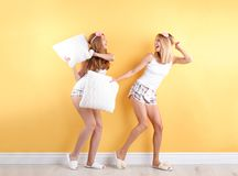 Two young women having pillow fight. Near color wall stock photos