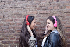 Two young women with headphones. Royalty Free Stock Images