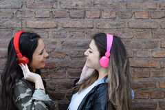 Two young women with headphones. Stock Photography