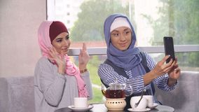 Two young women in hijabs do selfie on a smartphone. Muslim women in a cafe. Two young women in hijabs do selfie on a smartphone. Muslim women in a cafe Royalty Free Stock Images