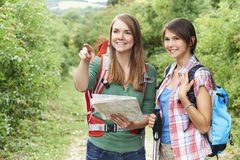 Two Young Women Hiking In Countryside Together Stock Image