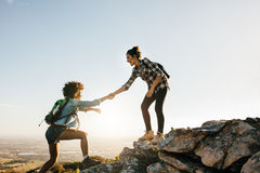Two young women hiking in nature. Young women helping friend to climb up the rock. Two young females hiking in nature Stock Photography