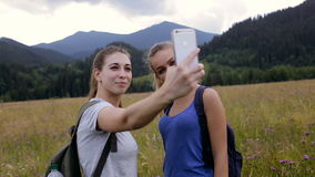 Two young women hiking take selfie portrait at mountain stock video footage