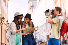 Two young women hold city map and guy with camera Royalty Free Stock Photos