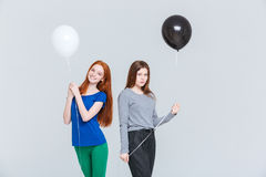 Two young women holding black and white balloons Royalty Free Stock Image