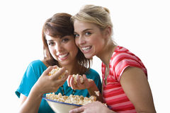 Two young women holding bowl of popcorn, smiling, portrait, cut out Royalty Free Stock Photos