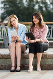 Two young women holding a digital tablet computers Royalty Free Stock Photography