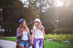 Two young women holding hands walking in green park. Best friends. Two young women best friends walking on summer day in green park royalty free stock images