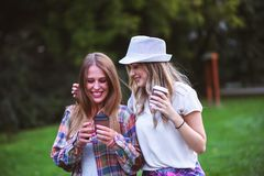 Two young women holding hands walking in green park. Best friends. Two young women best friends walking on summer day in green park stock photos