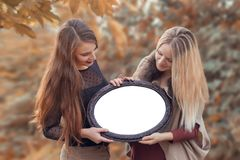 Two young women holding a photo frame. Place for text. Mock-up Stock Images