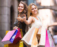 Two young women holding shopping bags Stock Photos