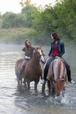 Two young women on horses stay in the water. Fog royalty free stock images