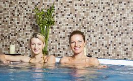 Two Young Women in Hot Tub. Two attractive, young women smile towards the camera while sitting in a hot tub. Horizontal shot stock image