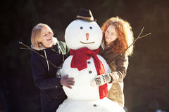 Two young women hugging snowman Stock Image