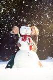 Two young women hugging snowman Stock Photos