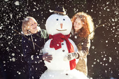 Two young women hugging snowman Stock Photos