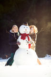 Two young women hugging snowman Royalty Free Stock Photography