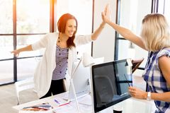 Two Young Women In Office Celebrating Success Stock Photo