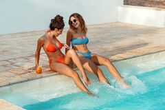 Free Two Young Women In Swimsuits Relaxing And Drinking Tropical Cocktails Stock Images - 217815874