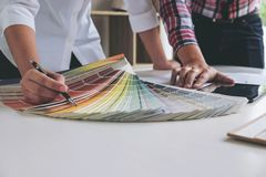 Two young women interior design or graphic designer working on p. Roject of architecture drawing with work tools and color swatches, colour chart in digital stock images