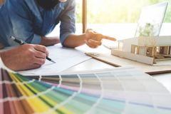 Two young women interior design or graphic designer working on p. Roject of architecture drawing with work tools and color swatches, colour chart in digital stock photos