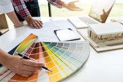 Two young women interior design or graphic designer working on p. Roject of architecture drawing with work tools and color swatches, colour chart in digital royalty free stock photo