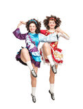 Two young women in irish dance dress dancing isolated. Two young women in irish dance dress and wig dancing isolated Royalty Free Stock Images