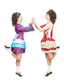 Two young women in irish dance dresses dancing isolated Stock Image