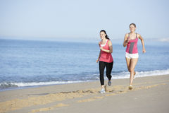 Two Young Women Jogging Along Beach Royalty Free Stock Image