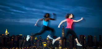 Two Young Women Jogging Through The Night Of New York Royalty Free Stock Images