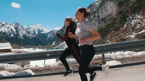 Two young women jogging on the road - Dolomites, Italy stock video footage