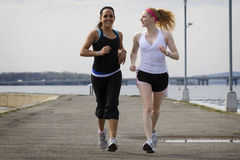 Two young women jogging together Royalty Free Stock Image