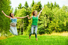 Two young women jumping stock photography