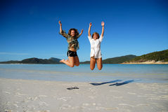 Two young women jumping on beach. Two beautiful young women jumping on beach with clear sky and ocean in background Stock Photos