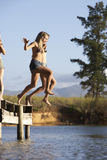 Two Young Women Jumping From Jetty Into Lake Stock Images