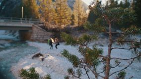 Two young women jumping near the rocky river with the backpacks and guitar under a bridge in the mountains stock footage