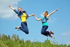 Two young women jumping Stock Image