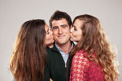Two young women kissing handsome man standing between them Stock Images