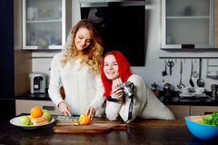 Two young women in the kitchen, chef and blogger.  Girl cut fruit. Two young girls in the kitchen talking and eating fruit Royalty Free Stock Photography