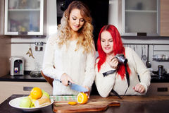 Two young women in the kitchen, chef and blogger.  Girl cut fruit. Two young girls in the kitchen talking and eating fruit Royalty Free Stock Photo