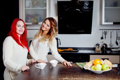 Two young women in the kitchen talking and eating fruit, healthy lifestyle, girls are going to do smoothies Royalty Free Stock Image