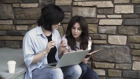 Two young women with a laptop working outside. Two young and beautiful women are sitting on a porch and working together. One is holding a laptop, the second is stock video