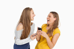 Two young women laughing while holding their cellphones. Against white background Royalty Free Stock Image