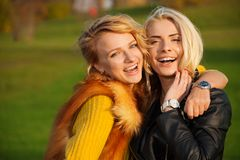 Two young women laughing in the park. Hugging and standing together royalty free stock images
