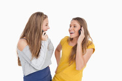 Two young women laughing on the phone together Stock Images