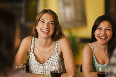 Two young women laughing in a restaurant Royalty Free Stock Photos