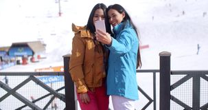 Two young women laughing at their selfie stock video footage