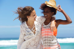 Two young women laughing together at the beach Stock Images