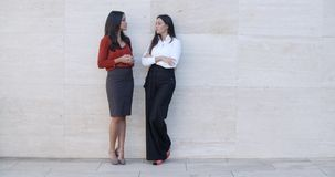 Two young women leaning on a wall chatting. Two fashionable young women standing leaning on a white wall chatting outdoors  bilateral copyspace stock footage